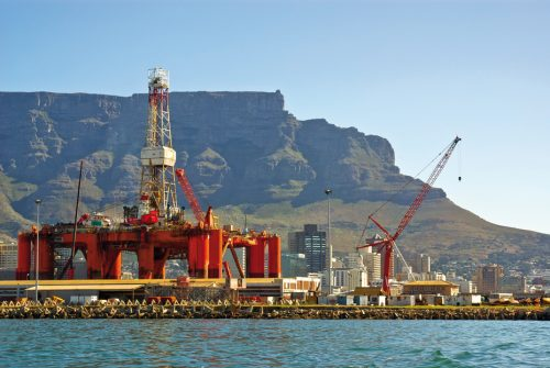 oil- rig in bay near mountains